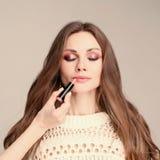 Model met gesloten ogen die terwijl stilist die make-up doen zitten stock afbeelding