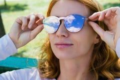 Model met het rode haar in de zonnebrilglazen Stock Foto