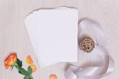 Model met prentbriefkaar en roze rozen op witte achtergrond kaart en roze bloemen inktpen, inkt, zegel, parfum en lint stock foto