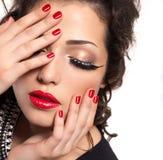Model met rode spijkers, lippen en creatieve oogmake-up Royalty-vrije Stock Afbeeldingen