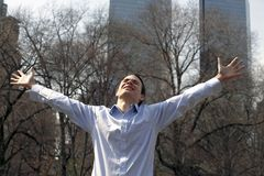 Model Michael Dow 1750. Young man in praise and celebration in NYC.  Photographed in Central Park while he lifted his arms in joy.  He is in his twenties Stock Photography