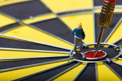 Model mini people walks towards the target on dart board. Royalty Free Stock Image
