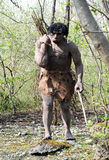 Model of Neanderthal Man Carrying Bundle of Sticks. Front View of Model of Neanderthal Man, an Extinct Species of Human, Carrying Bundle of Sticks Over Shoulder Stock Photo