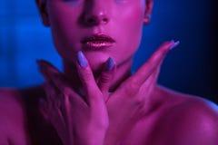 Model in neonschaduwen met heldere lippen om handen dichtbij het gezicht te houden stock afbeeldingen