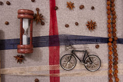 Model of an old bicycle hourglass and rudraksha. Model bicycle on a gray linen fabric with hourglass and rudraksha Royalty Free Stock Photos