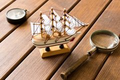 Model of old sailboat, old magnifying glass and compass on wooden background. Travel concept.  royalty free stock images