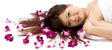 Model with Orchids. A young Asian woman lying on the floor with purple orchid flowers Stock Images