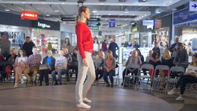 Model in pajama and white socks defiles the catwalk during a fashion show on background of audience stock video footage