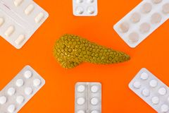 Model of pancreas gland surrounded by six blister packs with white pills on orange background.  Photo concept art of treatment or Stock Image