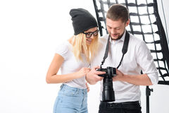 Model and photographer are looking through the. Time to check. Young attractive model and male photographer are looking through the taken photos stock photography