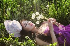 Model in a pink dress on a dandelion field in a straw hat Royalty Free Stock Photos
