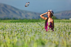 Model in a pink dress on a dandelion field in a straw hat Stock Photo