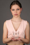 Model in pink top holding glass of water. Close up. Gray background Royalty Free Stock Photo