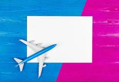 Model of airplane and blank sheet of paper on the blue and pink wooden background. Travel concept. Creative design. Royalty Free Stock Photo