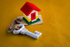 Model of plastic house with key and paper tag Stock Images