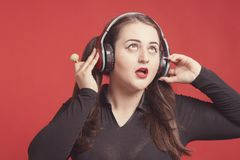 Model plus size with sweet donut, happy girl holding in hand candies and listen music in headphones, in black bodysuit. XXL. Female on red background royalty free stock photos