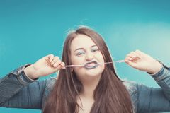 Model plus size with sweet donut, happy girl posing with gum in jeans jumper and bra. XXL female on blue background stock image