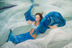 Model in a pool wearing a mermaid`s tail.