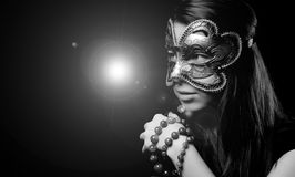 Model portrait. Portrait of a beautiful girl in black and white with carnival mask and ligh in background Royalty Free Stock Photography