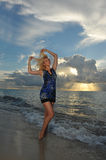 Model posing in beach dress at early morning sunrise Stock Photo