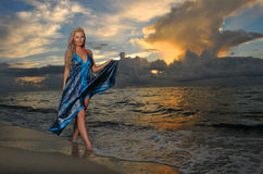 Model posing in beach dress at early morning sunrise stock photos