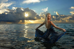 Model posing in beach dress at early morning sunrise royalty free stock images