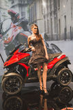Model posing at EICMA 2014 in Milan, Italy. MILAN, ITALY - NOVEMBER 5: Model poses with Quadro scooter at EICMA, international motorcycle exhibition on NOVEMBER Royalty Free Stock Image