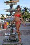 Model posing in front of old signpost. In Key West, FL Royalty Free Stock Photography
