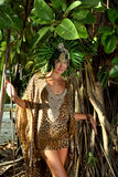 Model posing in front of tropical tree wearing animal print resort dress Royalty Free Stock Photo
