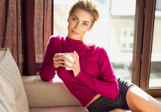 Model posing while holding mug. Attractive young woman in purple jumper and blue shorts posing on a settee while holding a mug Royalty Free Stock Photo