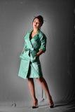 Model posing in light green raincoat standing in the studio. Retro style Stock Photos