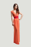 Model posing in orange dress. Model with beautiful long hair posing in orange dress isolated Royalty Free Stock Photos