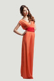 Model posing in orange dress. Model with beautiful long hair posing in orange dress isolated Stock Photos