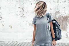 Model posing in plain tshirt against street wall. Hipster girl wearing blank gray t-shirt and backpack posing against rough street wall, minimalist urban Royalty Free Stock Images