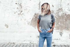 Model posing in plain tshirt against street wall. Hipster girl wearing blank gray t-shirt, jeans and backpack posing against rough street wall, minimalist urban stock photos