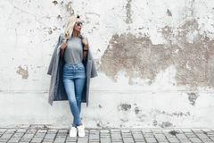 Model posing in plain tshirt against street wall. Hipster girl wearing blank gray t-shirt, jeans and coat posing against rough street wall, minimalist urban royalty free stock photography