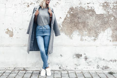 Model posing in plain tshirt against street wall. Hipster girl wearing blank gray t-shirt, jeans and coat posing against rough street wall, minimalist urban royalty free stock photo