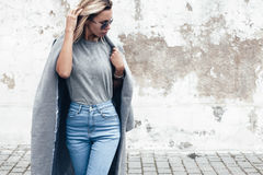 Model posing in plain tshirt against street wall. Hipster girl wearing blank gray t-shirt, jeans and coat posing against rough street wall, minimalist urban stock image