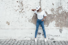 Model posing in plain tshirt against street wall. Hipster girl wearing blank white t-shirt, jeans and baseball cap posing against rough street wall, full length Royalty Free Stock Photography