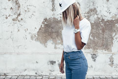 Model posing in plain tshirt against street wall. Hipster girl wearing blank white t-shirt, jeans and baseball cap posing against rough street wall, minimalist stock photo