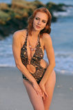 Model posing pretty at rocky beach in swimsuit. Model posing pretty at rocky beach in designers animal printed swimsuit Stock Image