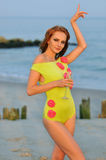 Model posing pretty at rocky beach in swimsuit. Beautiful woman with glass of champagne dancing on the beach in lime color designer's swimsuit Royalty Free Stock Photo
