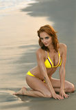 Model posing pretty at rocky beach in swimsuit. Beautiful woman sitting on the beach in yellow color designer's swimsuit Stock Image