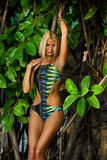 Model posing in front of tropical jungle tree Royalty Free Stock Photos
