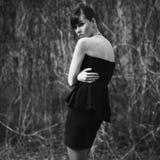 Model posing in short black dress. Brunette model posing in short black dress royalty free stock images