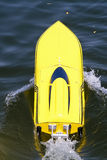 Model power boat. A remote controlled yellow model power boat on water royalty free stock images