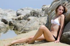 Model przeciw skałom jest ubranym czarny i biały bikini Obraz Royalty Free