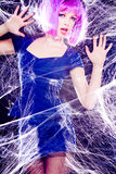 Model with purple wig and intense make-up trapped in a spider web Royalty Free Stock Photography