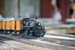 Toy Train on the Track and Model Railroad Exhibit. Model Railroad exhibit. Train on Track. Old Engine, Yellow box cars royalty free stock images