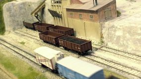 Model railroad track. Cargo station in quarry. Rail transportation, entertainment toy industry. Model railroad track. Cargo station in quarry. Miniature train stock video